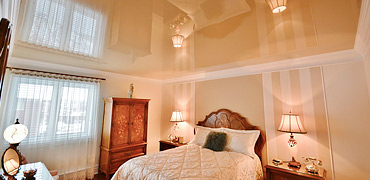 Глянцевый натяжной потолок в спальной